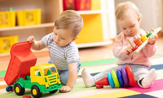 Kids play with educational toys. Children sit on a rug in a play room at home or kindergarten. Toddler boy with toy lorry and baby girl with rings.