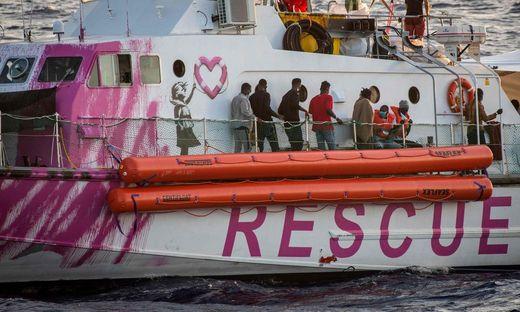 Migranten stehen an Bord des  vom britischen Street-Art-Künstler Banksy bemalten und finanzierten