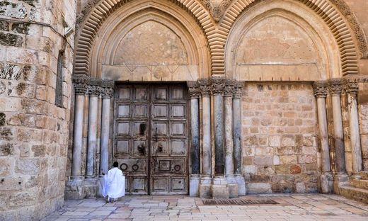 Ein Pilger kniet vor dem verschlossenen Tor der Grabeskirche in Jerusalem
