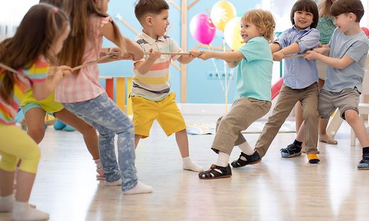 Group of children in a rope-pulling contest in day care centre