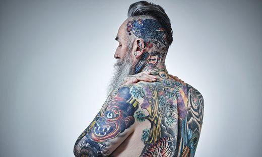 Heavily tattooed mature male