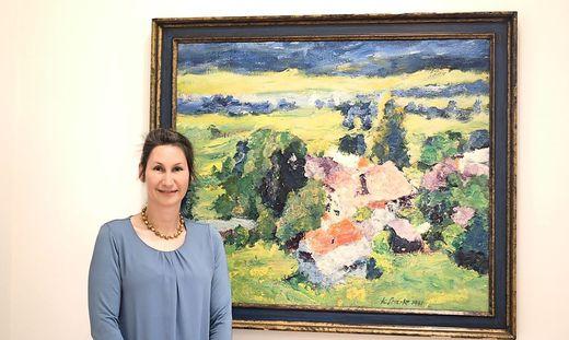 """Sigrid Diewald vor einem Bild von Karl Stark (""""Sonnige Landschaft mit roten Dächern"""")"""