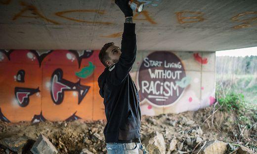 """Die Antidiskriminierungsstelle setzt ein Zeichen: Sprayer Oliver Naimer, alias """"KEOS"""", beim Übersprühen von rassistischen Graffiti"""