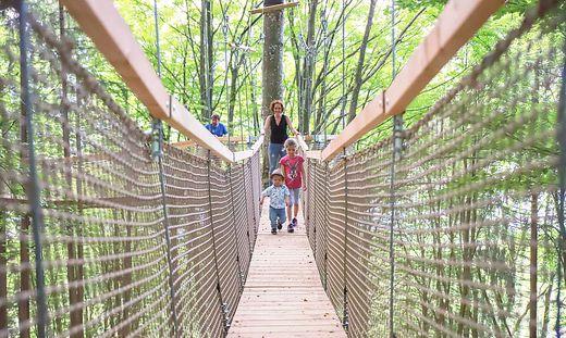 Mutter mit zwei Kindern geht über eine Hängebrücke im Familywald Ossiacher See