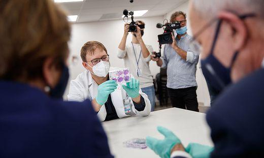 Virologe Florian Krammer zeigt dem Bundespräsidenten Influenza-Viren