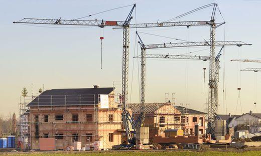 Neubaugebiet mit vielen Häusern im Rohbau und Baukräne