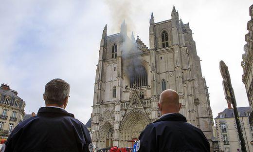 Männer schauen auf die brennende Kathedrale