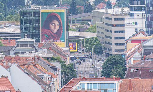 """Sogar vom Schloßberg aus zu sehen: Das Bild """"Afghan Girl"""" auf einem riesigen Werbeplakat für die aktuelle Fotoausstellung in Graz"""