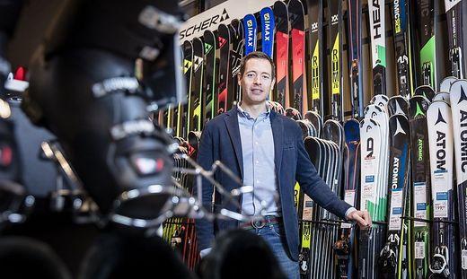 SCHMITZ Thorsten, Geschäftsführer der Intersport Austria GmbH, blickt mit Wintersportequipment im Hintergrund in die Kamera