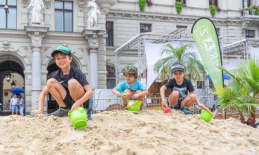Vor dem Rathaus haben kleine Grazer derzeit in der größten Sandkiste der Stadt alle Hände voll zu tun