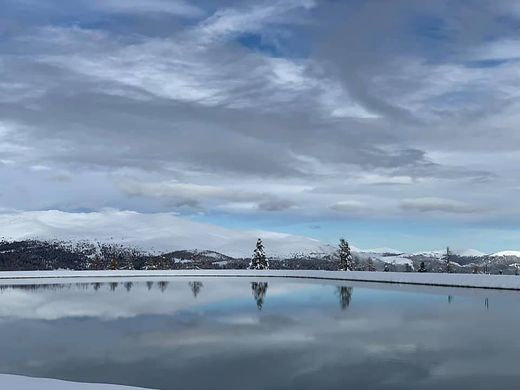 Blick über den neuen Beschneiungsteich auf der Hochrindl in die verschneite Umgebung