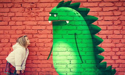 happy young girl smiling to imaginary monster friend painted on outdoor wall