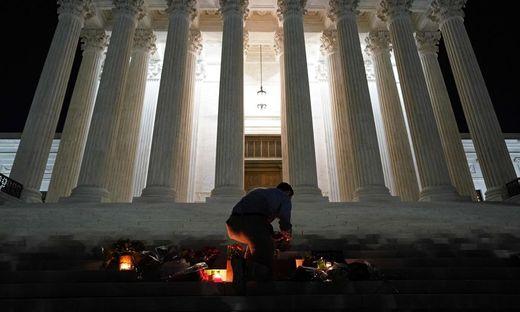 Im Andenken an die verstorbene Richterin Ruth Bader Ginsburg entzündet ein Mann vor dem Supreme Court in Washington eine Kerze