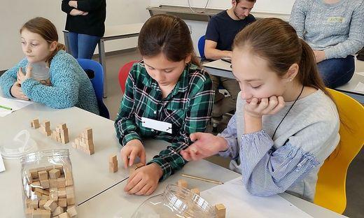 Schülerinnen experimentieren in der Mathematikwerkstatt der PH Kärnten. Solche Zugänge helfen auch beim Verständnis von Bruchrechnen