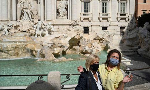 Touristinnen posen vor dem berühmten Trevi-Brunnen in Rom