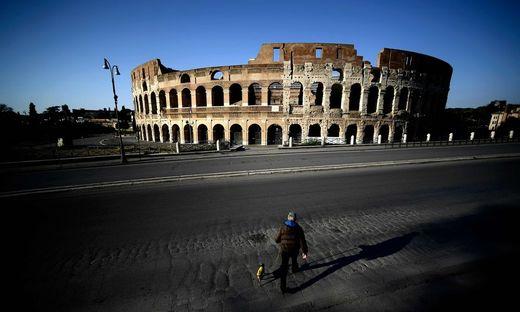 Ein einsamer Spaziergänger mit Hund vor dem Kolosseum in Rom