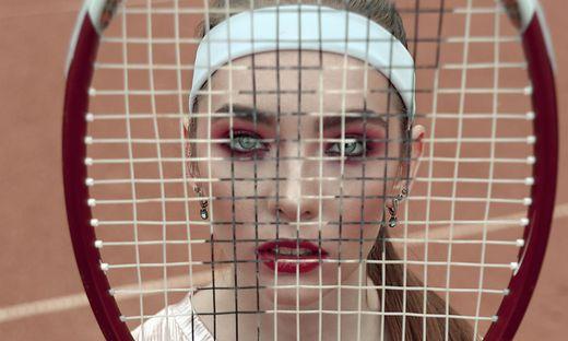 yonug girl loking through tennis racquet. Fashion sport conseptual look