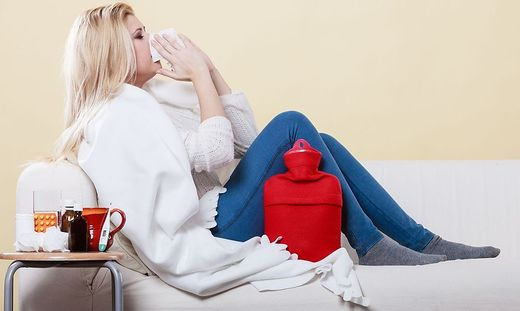 Woman being sick having flu lying on sofa