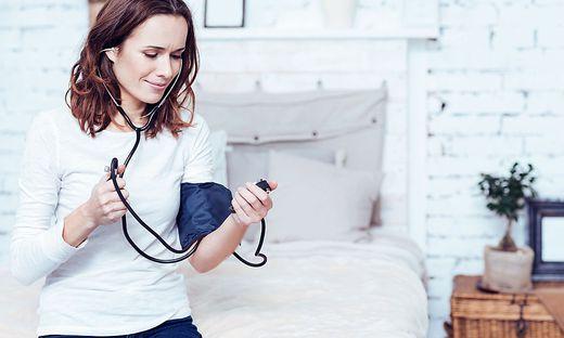 Involved young woman using tonometer at home