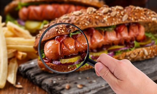 Magnifying glass examining hot og