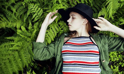 Pretty young blond girl hipster in hat among fern, vacation in green forest