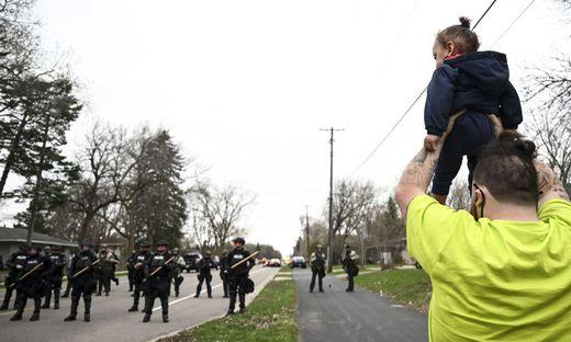 Der Bruder von Daunte Wright hält Wrights Sohn in die Höhe, als die Polizisten in Richtung Demonstranten marschieren