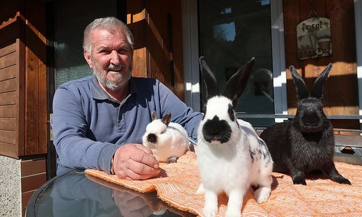 August Friedl mit drei seiner Kaninchen