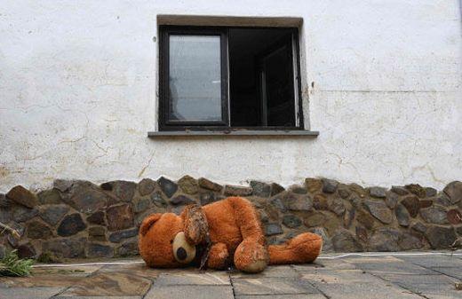 Ein mit Schlamm beschmierter Teddybär vor einem Haus in Schuld.