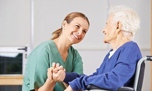 Krankenschwester haelt Hand einer Seniorin