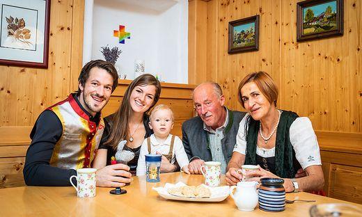 Familie Warmuth sitzt gemeinsam um den Esstisch in den Wohnräumen des Hofes