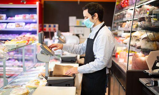 Shopkeeper running business while wearing mask, coronavirus pandemic concept