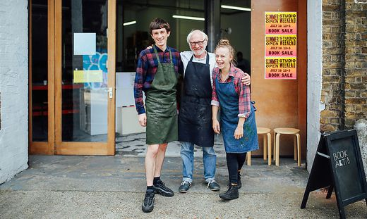 Family portrait of senior craftsman with daughter and son outside print workshop