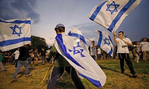 Jüdische Kinder schwenken in der Siedlung Mehola im Jordantal israelische Flaggen
