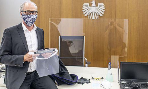 Der Klagenfurter Bezirksgerichtschef Waldner hält ein Vollvisier in den Händen