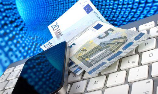 Euro Geldscheine und Smartphone auf einer Tastatur vor Datentunnel des Internets