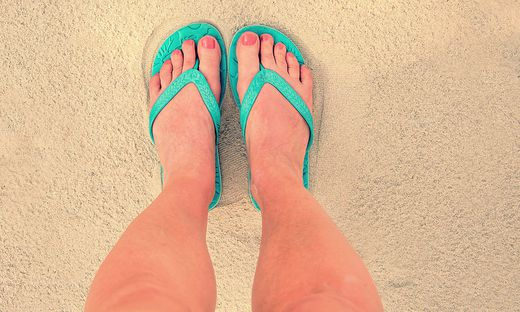 Selfie of woman feet wearing flip flops on a beach, vintage process