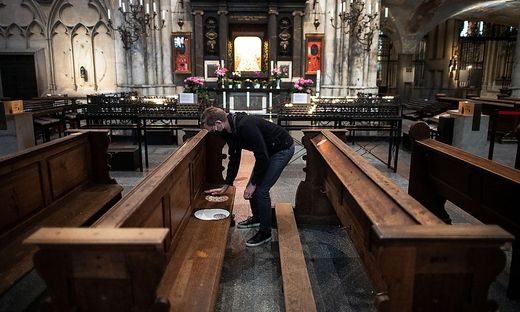 Damit die Gläubigen genug Abstand halten, werden die Plätze in den Kirchenbänken markiert