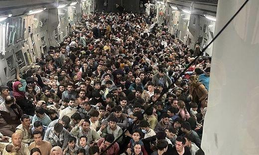 """Die Internetseite """"Defense One"""" veröffentlichte am Montag ein Foto des vollgepackten Innenraums der Transportmaschine vom Typ C-17, in dem die Afghanen auf dem Boden sitzen - der vor lauter Menschen nicht mehr zu sehen ist."""