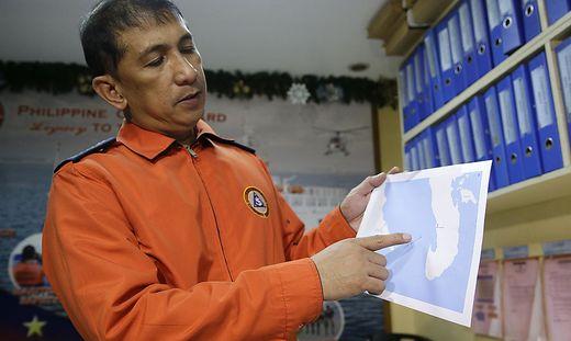 Ein Mitarbeiter der Küstenwache zeigt auf die Unglücksstelle