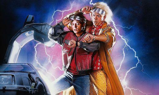 """Bekannte Zeitreisende in der """"Zurück in die Zukunft""""-Trilogie: Marty McFly (gespielt von Michael J. Fox) und  Dr. Emmett """"Doc"""" Brown (dargestellt von Christopher Lloyd)"""