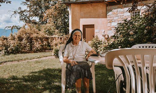 Schwester Lucia genießt im Garten die Sonne