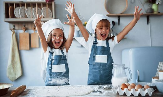 Having fun during the process. Family kids in white chef uniform preparing food on the kitchen