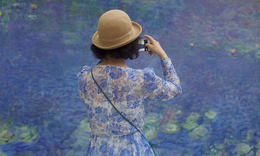 Eines der bekanntesten Bilder von Stefan Draschan: Die Frau im blauen Kleid vor einem Bild von Claude Monet im Musée de l'Orangerie in Paris
