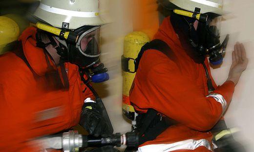 Zwei Feuerwehrleute unter Atemschutz bei der Durchsuchung eines Gebaeudes - Two firemen with breathing protection at a practice of looking for missed people in a building