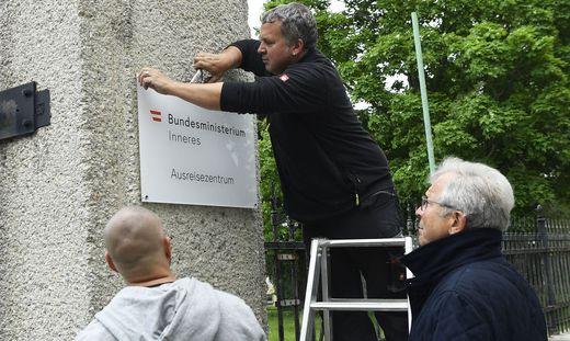 """Der ehemalige Flüchtlingskoordinator Ferry Maier und ein Team der Plattform """"Menschen.Würde.Österreich"""" haben am Donnerstag die """"Ausreisezentrum""""-Tafel bei der Erstaufnahmestelle für Asylwerber in Traiskirchen abmontiert"""