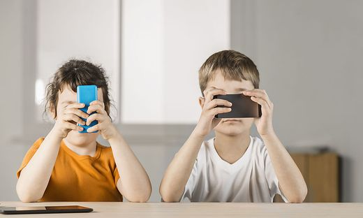 Brother and sister using mobile phones at home