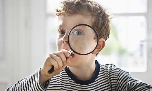 Boy (7-9) with magnifying glass