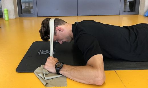 Verschiedene Übungen mit dem Theraband können helfen, die Muskulatur im Nacken zu stärken.