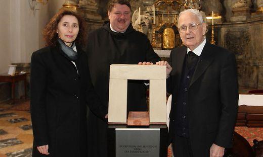 Roswitha Dautermann mit Pater Egon und Seelsorger Josef Gölles vor ihrem Kunstobjekt.
