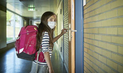 Girl wearing mask in school opening classroom door